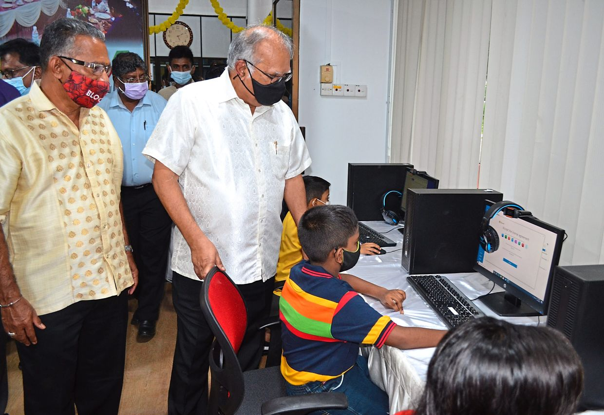 Ramasamy (white shirt) and Gunasegaran observing a child using the facilities at the new ICT Learning Centre next to the library.