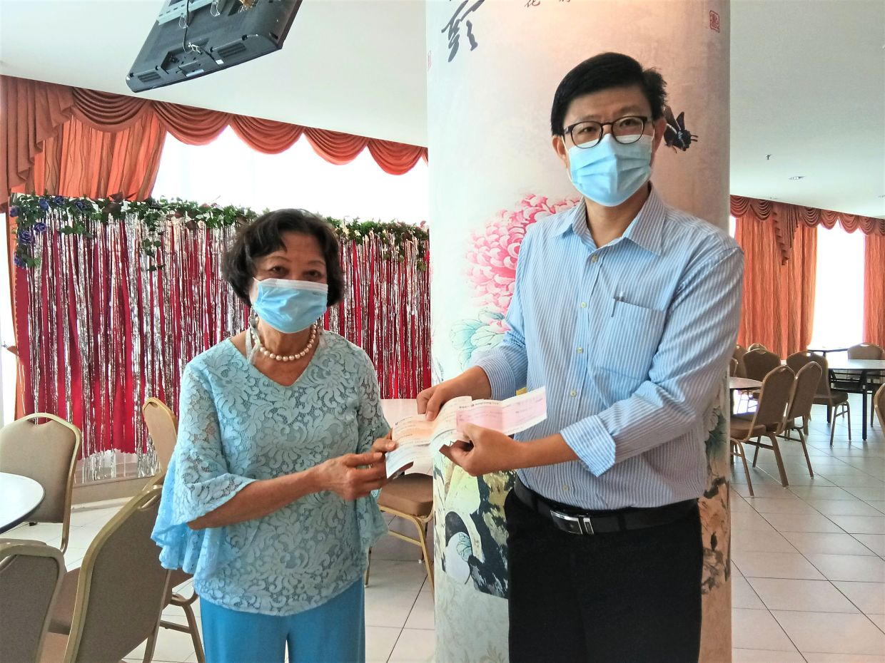 Prof Dr Choong (right) receiving a cheque from Mun Fah.