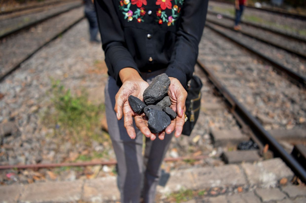 Pereira holds pieces of coal fallen onto railway tracks from a cargo train at the Kulem railway station in Goa.