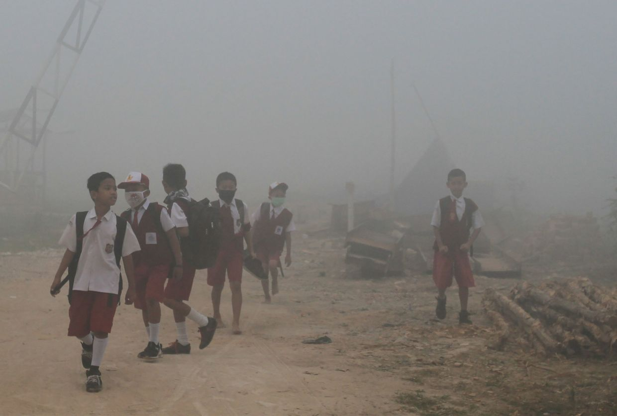 Schoolchildren make their way to school as haze from forest fires blanketing Palembang in 2019. — AFP