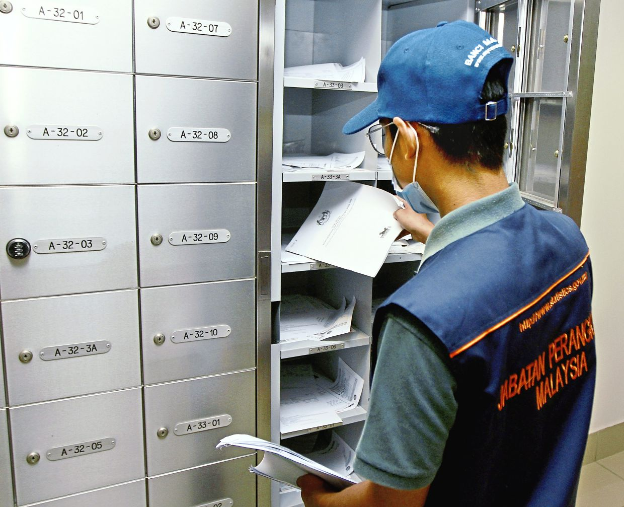 An emunerator placing census survey forms in the post boxes of a condominium.