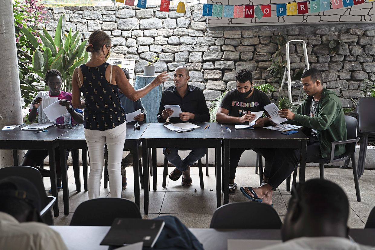 Moroccan and West African migrants take part in an English language class offered by volunteers at the Holiday Club Puerto Calma hotel.