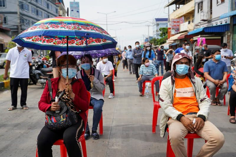 People wait in line before being vaccinated against coronavirus disease (COVID-19) in Phnom Penh, Cambodia. - Reuters