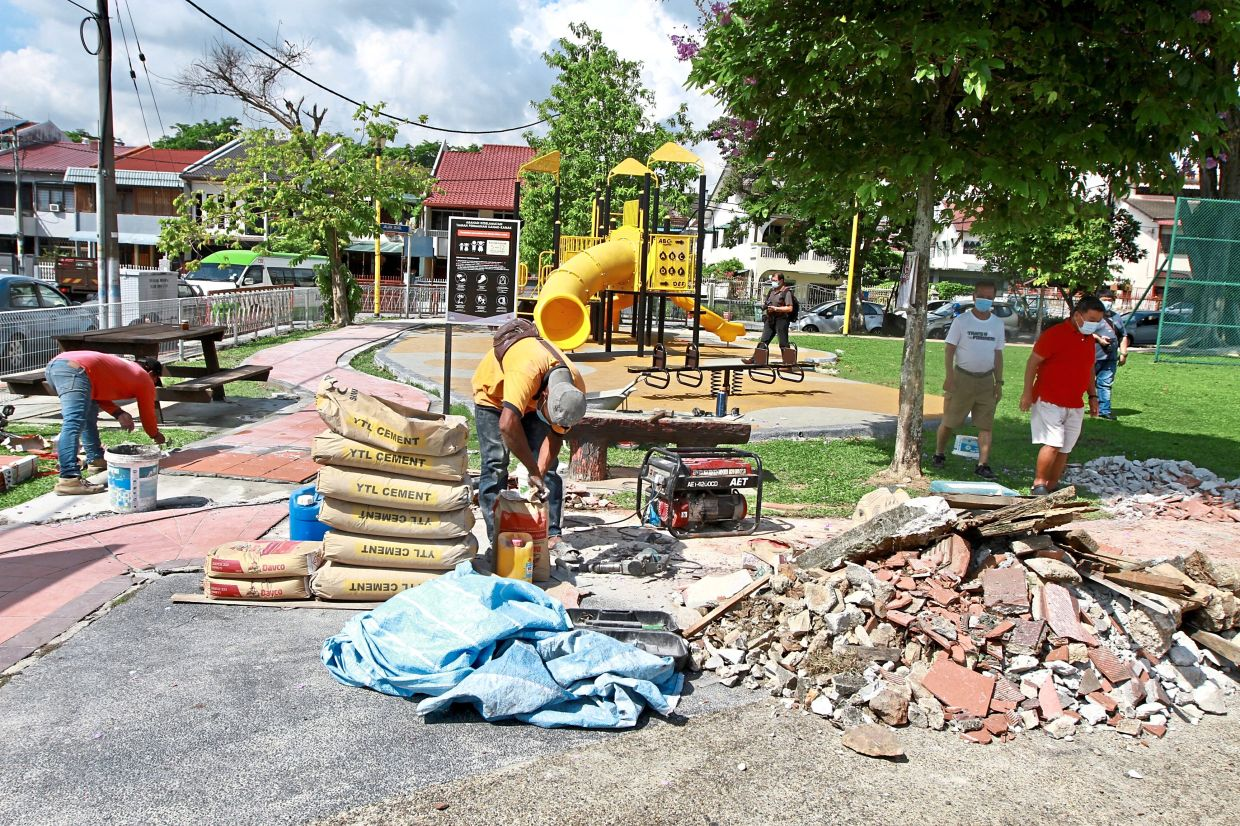 Workers laying out the new pavement next to the playground in Taman Batu.