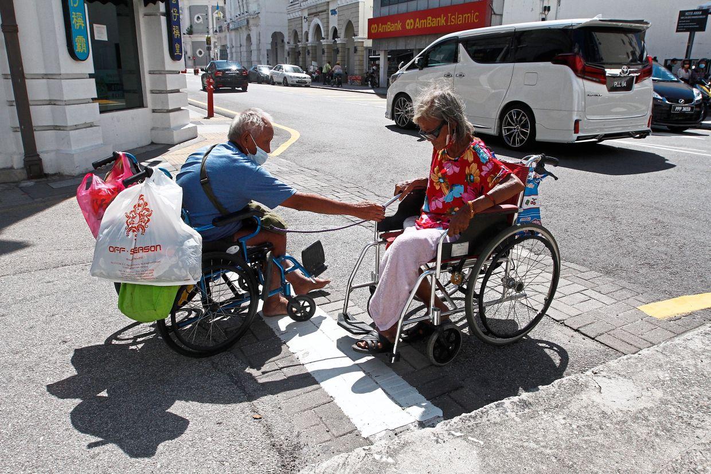 Doing it their way: Using an elastic cord to connect their wheelchairs, Lim (left) tows Ng's wheelchair along Beach Street in George Town. — ZHAFARAN NASIB/The Star