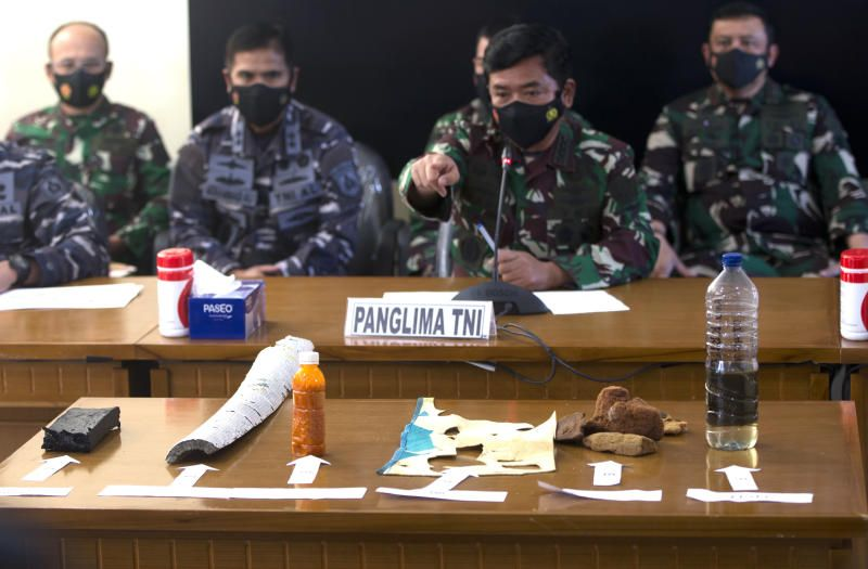 Indonesian Navy Chief Yudo Margono, front left, Indonesian Military chief Hadi Tjahjanto, center, and Indonesia police chief Listyo Sigit Prabowo, right, talk to media as they display debris found in the waters during a search for the Indonesian Navy submarine KRI Nanggala at Ngurah Rai Military Air Base in Bali, Indonesia on Saturday, April 24, 2021. Indonesia's navy on Saturday said items were found from a missing submarine, indicating the vessel with 53 crew members had sank and there was no hope of finding survivors. - AP