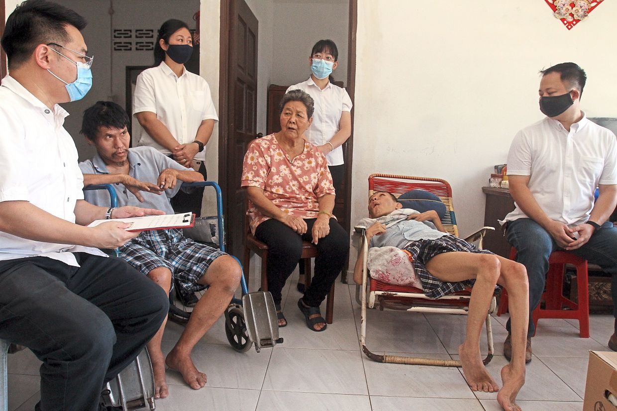 In need of help: Liew (left) visiting Chew (centre) and her sons Yew Leong (second from left) and Yew Ming at their home in Buntong, Ipoh.