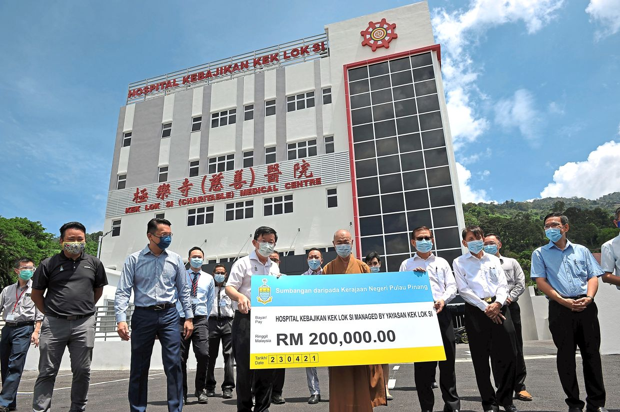 Chow (third left, in white) presenting the state aid of RM200,000 to Ooi (third right) during a visit to the Kek Lok Si Charitable Medical Centre. With them are (from left) Ng, Yeoh, Ven Seck, Dr Teng and Wong.