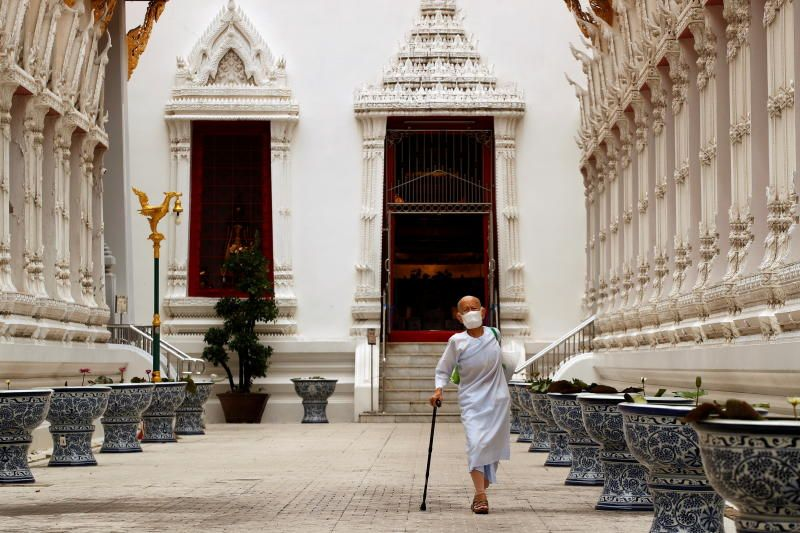 A buddhist nun wearing a face masks walks at Wat Mahathat Yuwaratrangsarit temple as the country struggles with a third wave of infections of the coronavirus disease (COVID-19) outbreak in Bangkok Thailand April 26, 2021. - Reuters