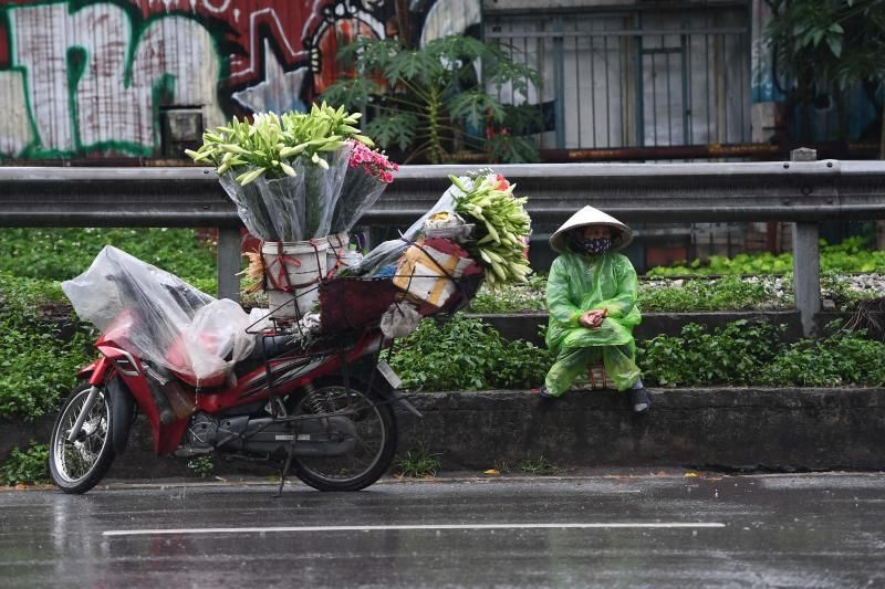 A street vendor waits for customers to buy flowers by her motorbike in Hanoi on April 26, 2021. - AFP