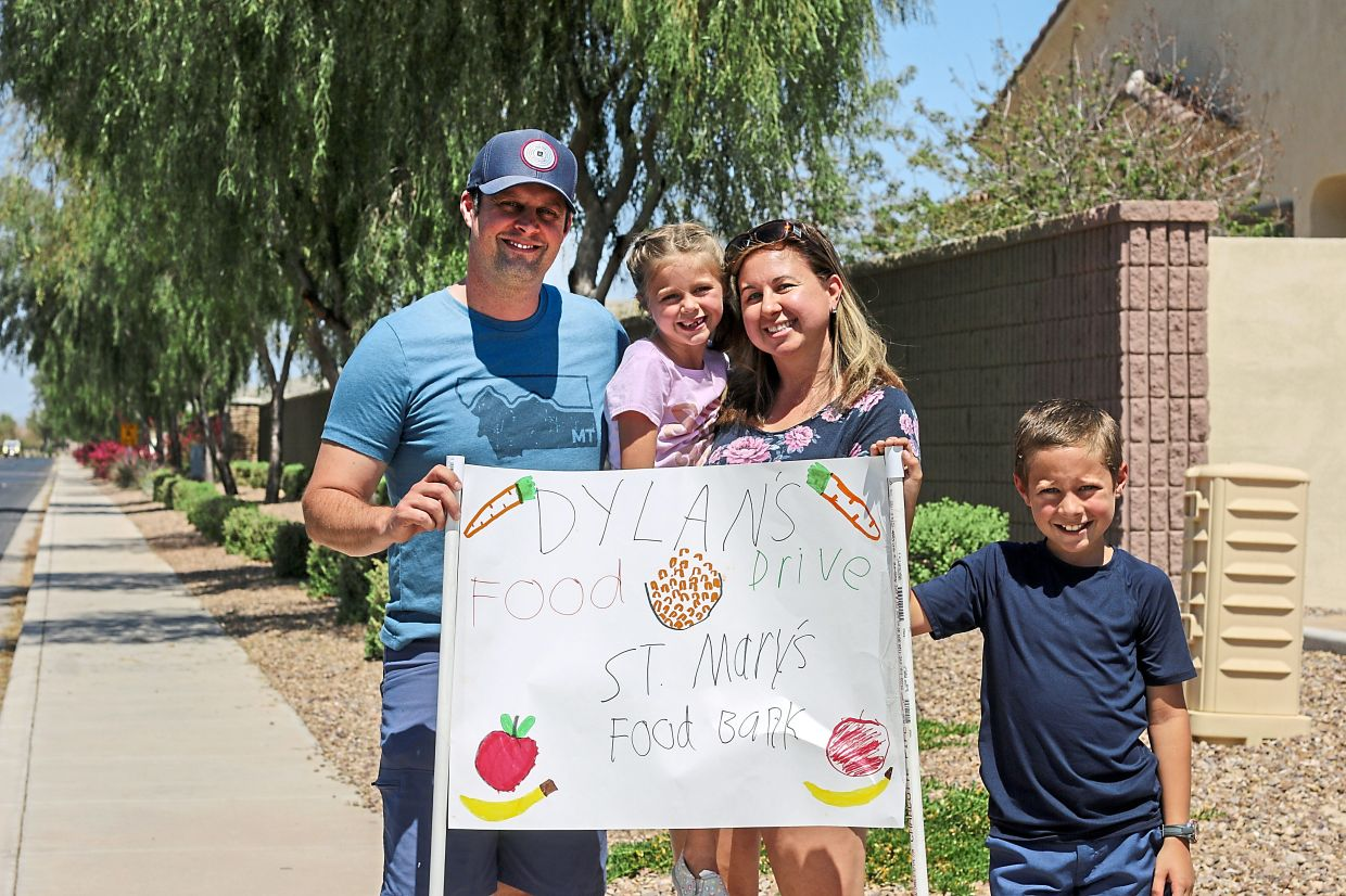 Nick (left), Evelyn, Erin (second from right) and Dylan Pfeifer (right) near their home in Chandler, holding a hand-drawn sign promoting a food drive recently.