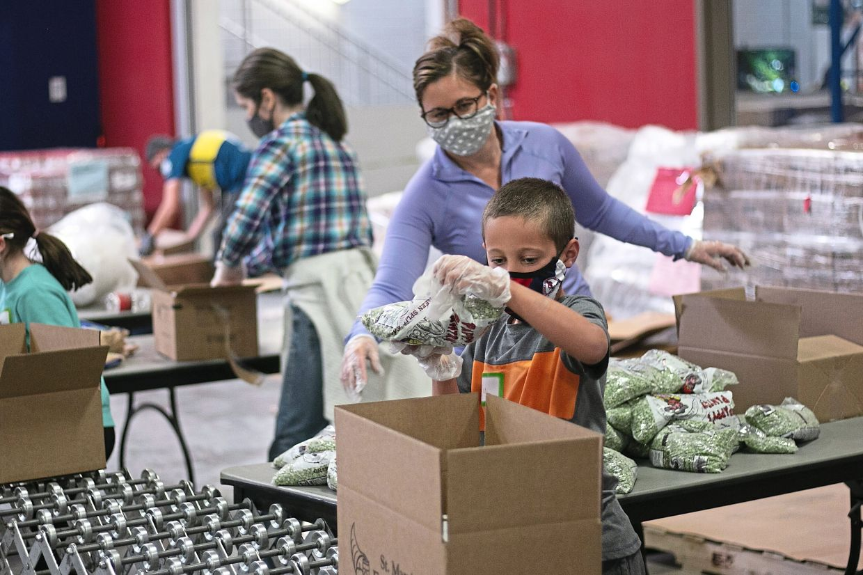 Erin (second from right) unloading boxes of bagged peas as Dylan places them into the boxes at St Mary's Food Bank in Phoenix.