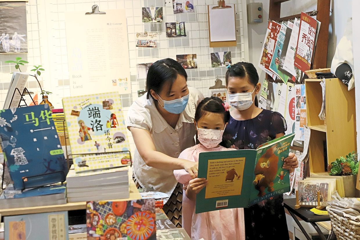 (From left) Wong reading a book  to her daughters Wen Hui, seven, and Wen Si, 10, at Book island.