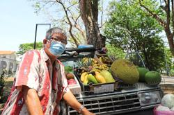 Man bent on selling fruits by roadside