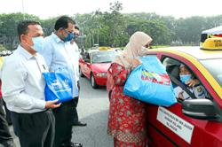 Taxi and bus drivers receive food baskets in Klang