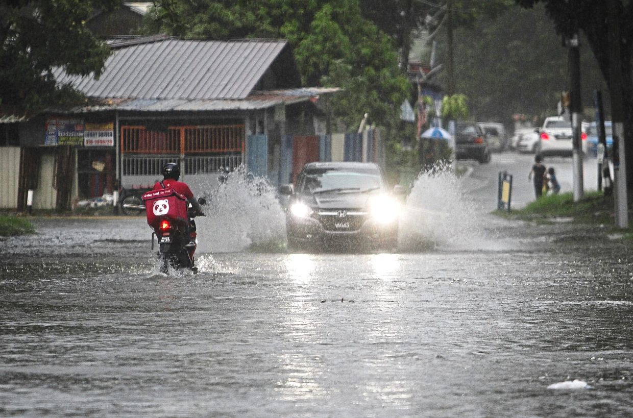 Flash floods after a downpour in Jalan P. Ramlee in April last year. — Filepic