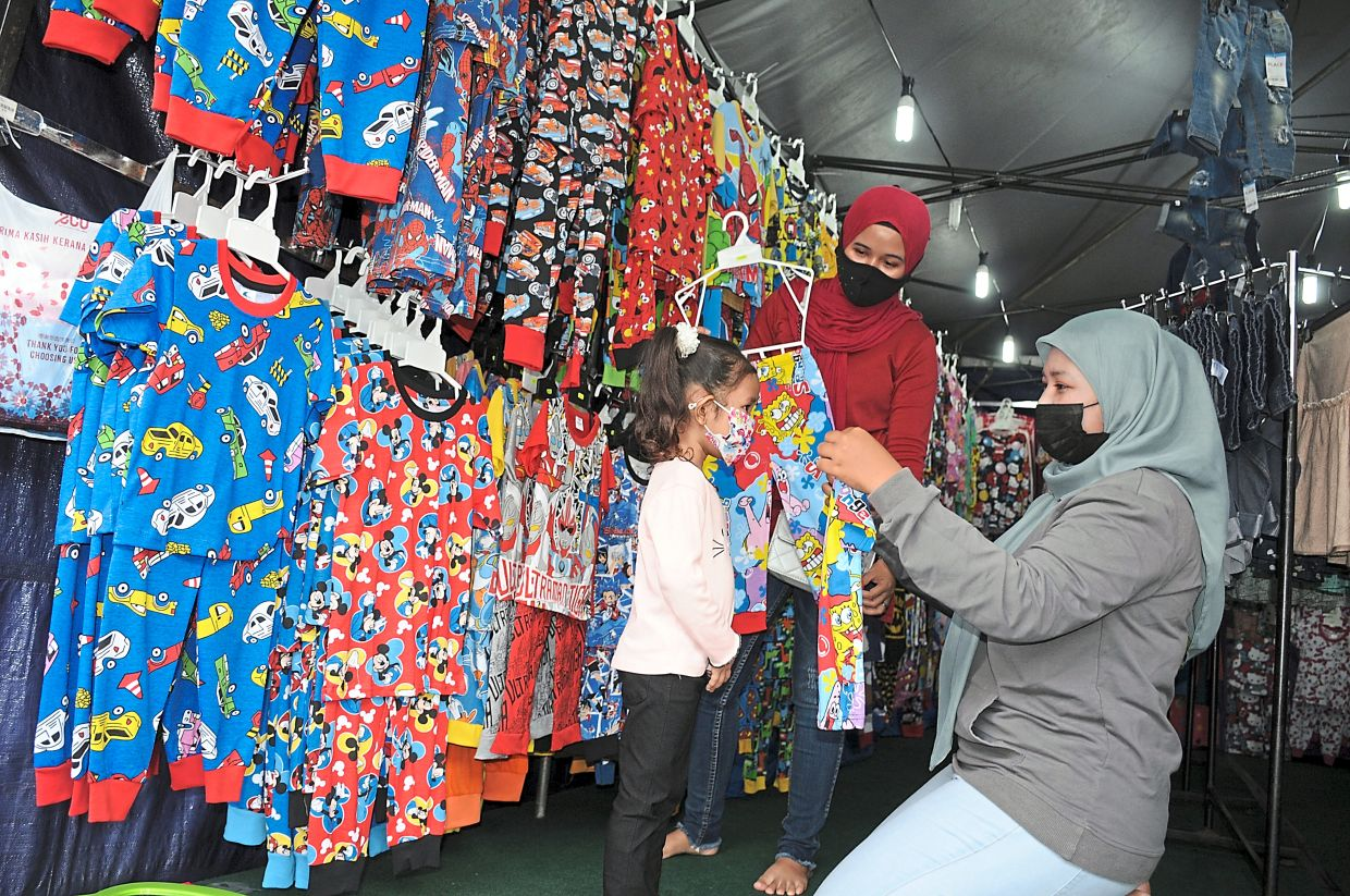 Nur Natasya (right) showing a cartoon character jumpsuit to Nur Iman.