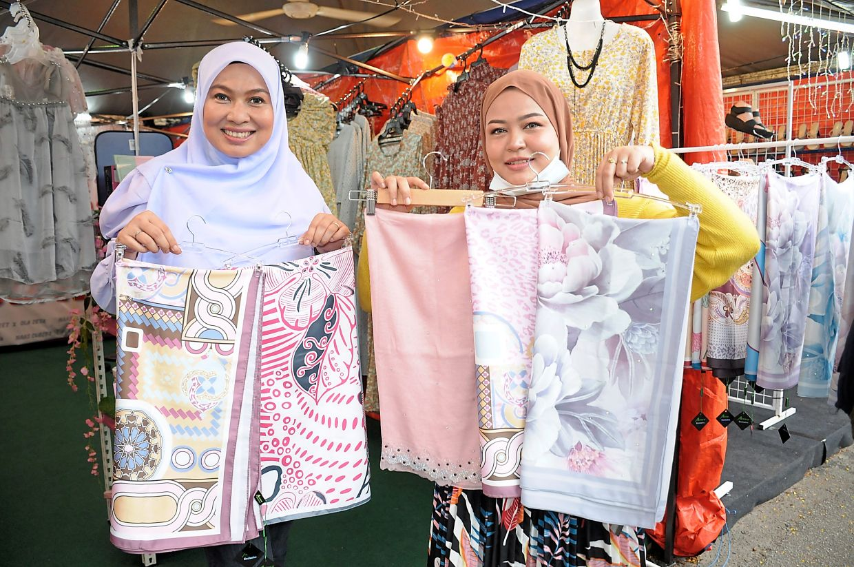 Ilaraz (right) and Ku Zetty displaying several headscarfs outside their stall.