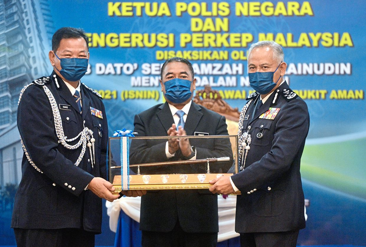 Passing the baton: Acryl Sani (right) is the new IGP, taking over from Abdul Hamid (left). He became the country's 13th IGP after a handing-over ceremony at Bukit Aman yesterday. — RAJA FAISAL HISHAN/The Star