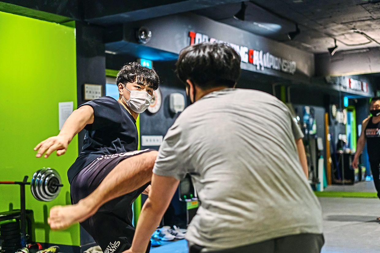 North Korean YouTuber Jang Jung Hyuk (left) practising mixed martial arts moves with his workout partner, Sim Min Seop, at a gym in Seoul.