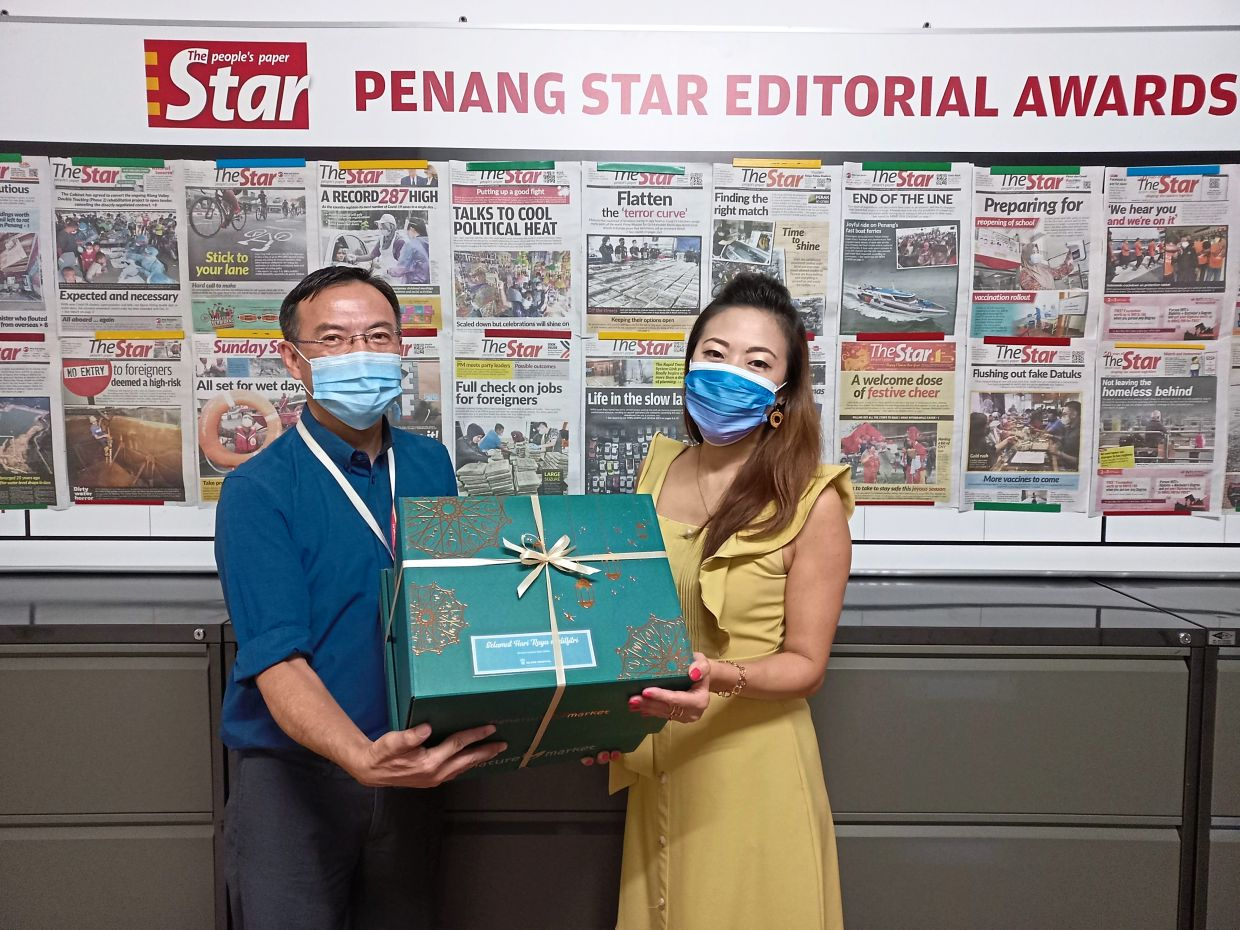 Goh (right) from Island Hospital handing over Raya goodies to Teng.