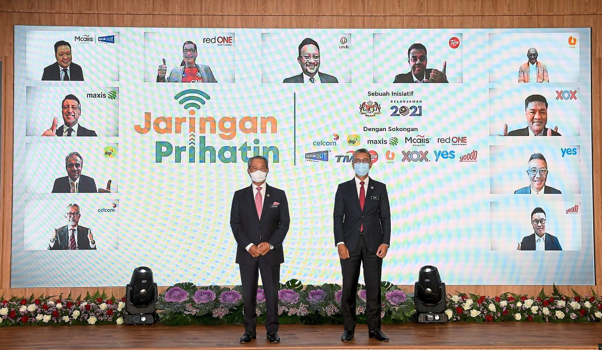 We're with you: Muhyiddin (left) posing with Tengku Zafrul, with the virtual participation of 11 representatives from local telco operators at the launch of the Jaringan Prihatin programme in Putrajaya. — Bernama