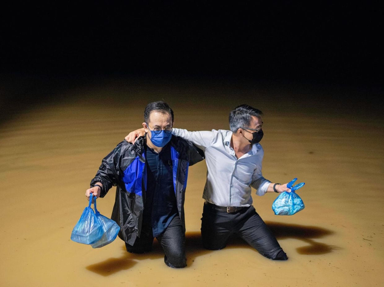 Bukit Mertajam MP Steven Sim (in black raincoat) and Machang Bubok assemblyman Lee Khai Loon (in white shirt) wading through the floodwater to distribute food to villagers at their homes during the flood on May 5, 2021.