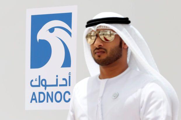 An Emirati man is seen near the logo of ADNOC in Ruwais, United Arab Emirates
