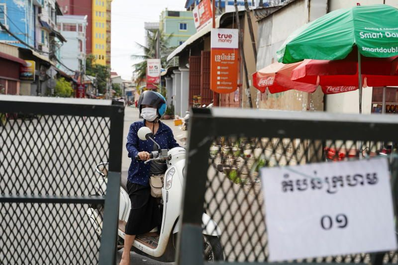 A woman riding a motorbike stops in front of barricades as authorities retained tighter curbs in some districts where infections have surged, amid the coronavirus disease (Covid19) outbreak, in Phnom Penh, Cambodia, May 6, 2021. - Reuters