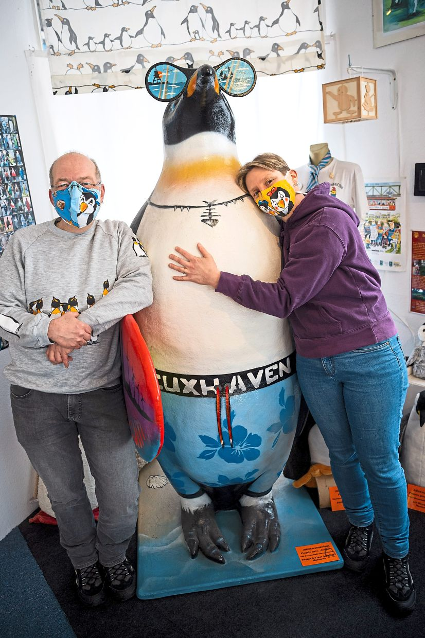 Kirchhoff (left) and Berends posing with a large penguin statue at their museum dedicated to the flightless birds in Germany.