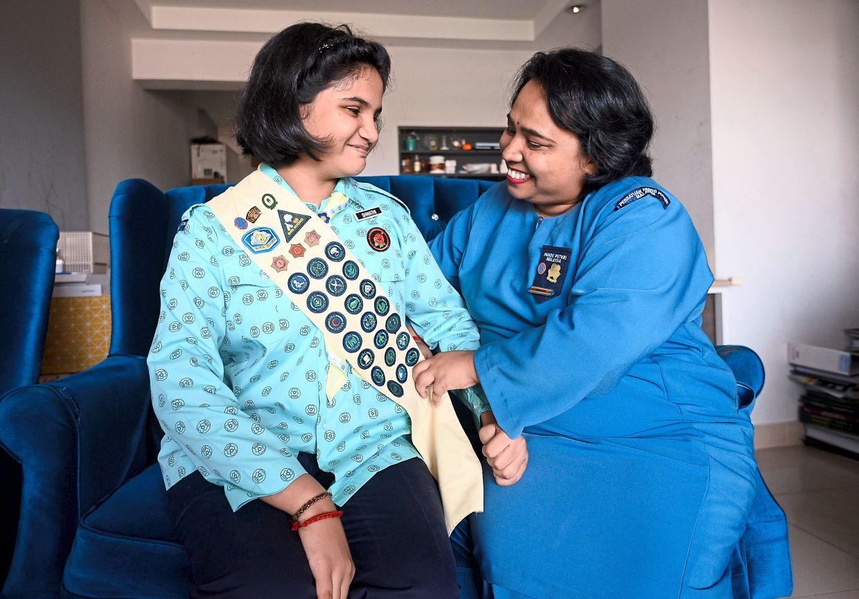 Sri Devi (right) putting her Girl Guides sash on her daughter Shwathi.