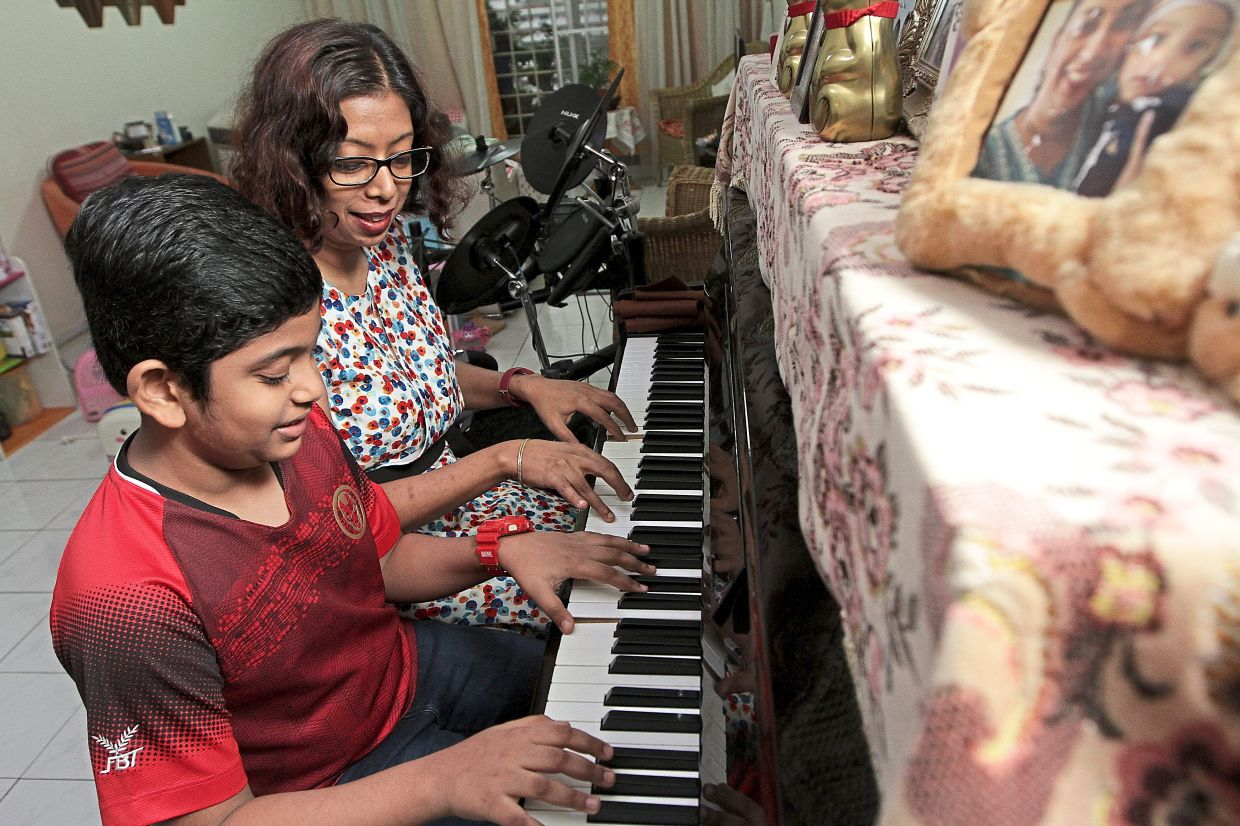 Gregory practising his scales with his mother Jessica on the piano she used as a child.