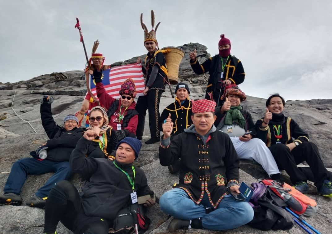 Sabah Deputy Chief Minister Datuk Seri Jeffrey Kitingan (sunglasses) with some of his expedition members posing for a group photo at the summit of Mount KInabalu.
