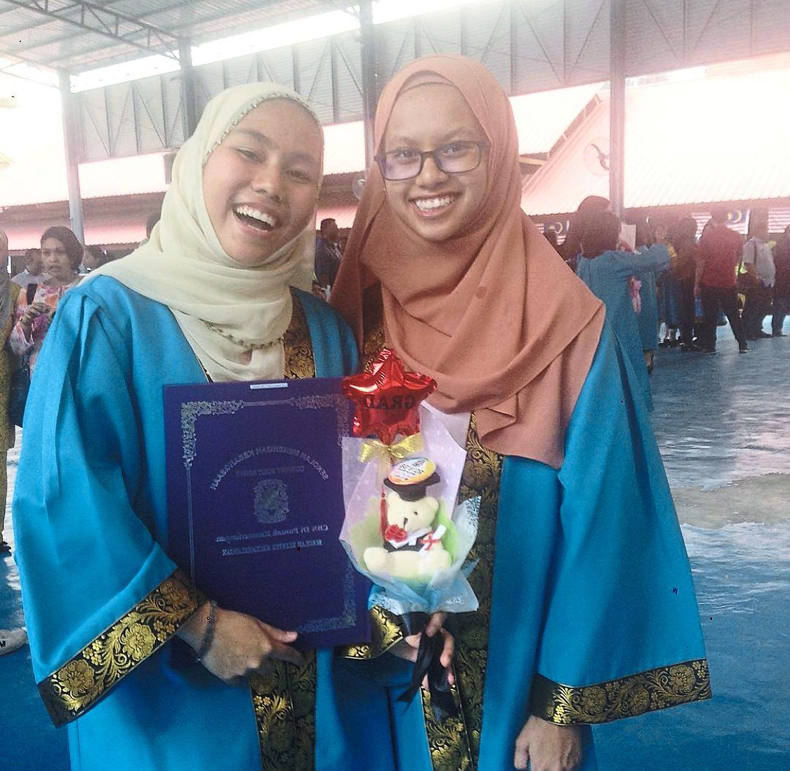 Buoyant spirits: Nurfatihah (right) and her friend Kamilia celebrating their graduation in 2018.