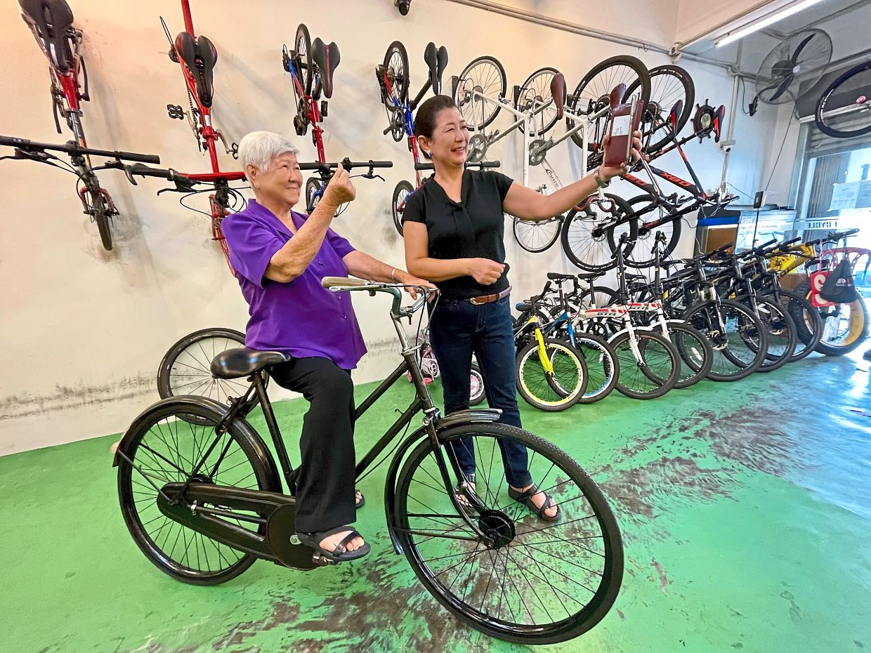 Sentimental value: Lee and her mother Yap taking a wefie after receiving the refurbished vintage bicycle. — FAIHAN GHANI/The Star
