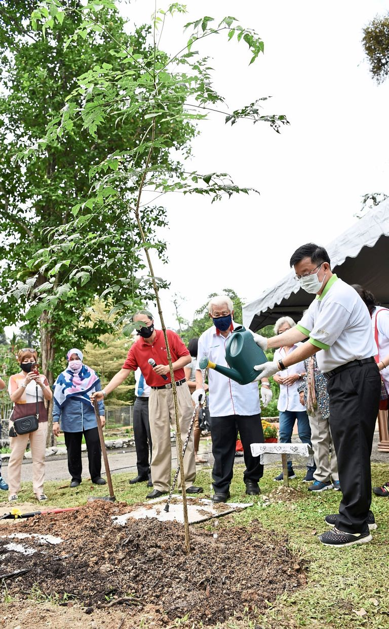 Chow watering the jasmine tree sapling at the event.