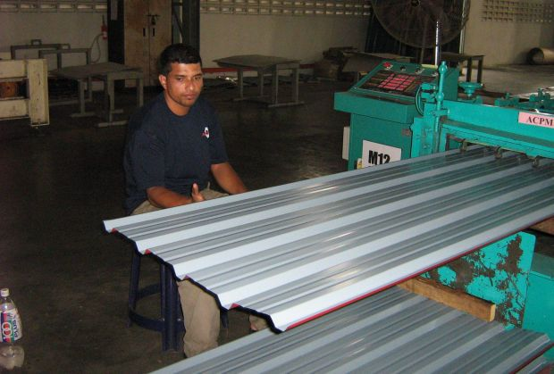 Employee of Astino Bhd working on roofing materials at the production floor of the group\'s plant.