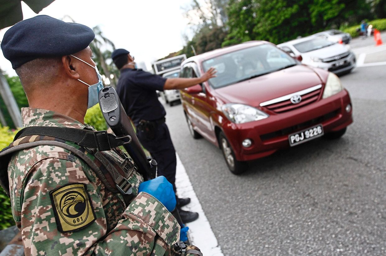 Armed personnel joining the police at a roadblock in Penang.