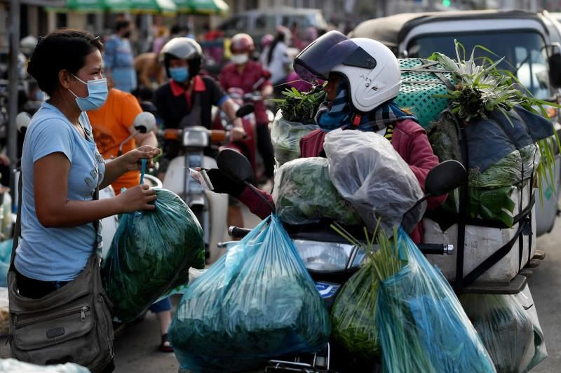 A woman buys vegetable along a street as markets remained closed amid lockdown restrictions introduced to try to halt a surge in cases of the Covid-19 in Phnom Penh on May 11, 2021. - AFP