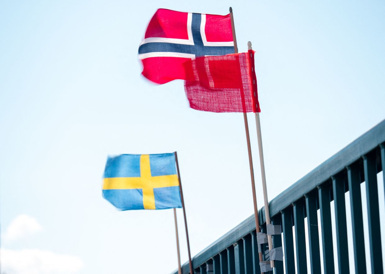 A Swedish flag on the Swedish side (left), a Norwegian flag on the Norwegian side and in the middle, a red flag marking the international workers' day set by the Berglund brothers wave in the wind on the old bridge of Svinesund Svinesund, Norway, on May 1.