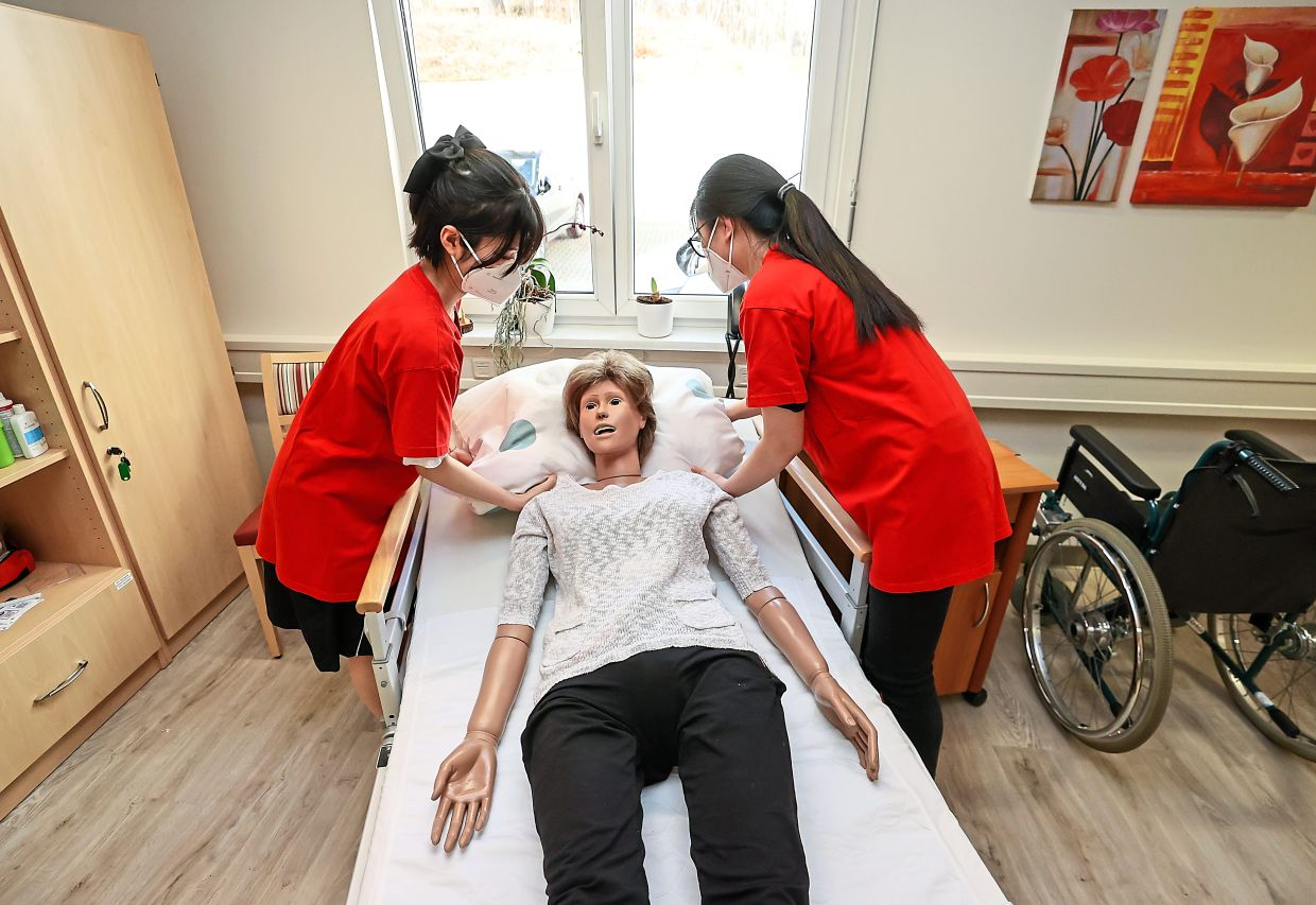 Vietnamese nurses Phung and Nguyen taking care of training dummy Elvira though now, they work as skilled nursing staff in Germany's eastern Vogtland region.