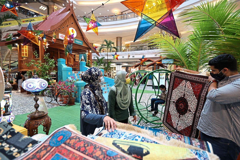 Shop owner Ahmad Jomaa showing a Turkish carpet to customers at 1Utama Shopping Centre in Petaling Jaya. — SAMUEL ONG and GLENN GUAN/The Star