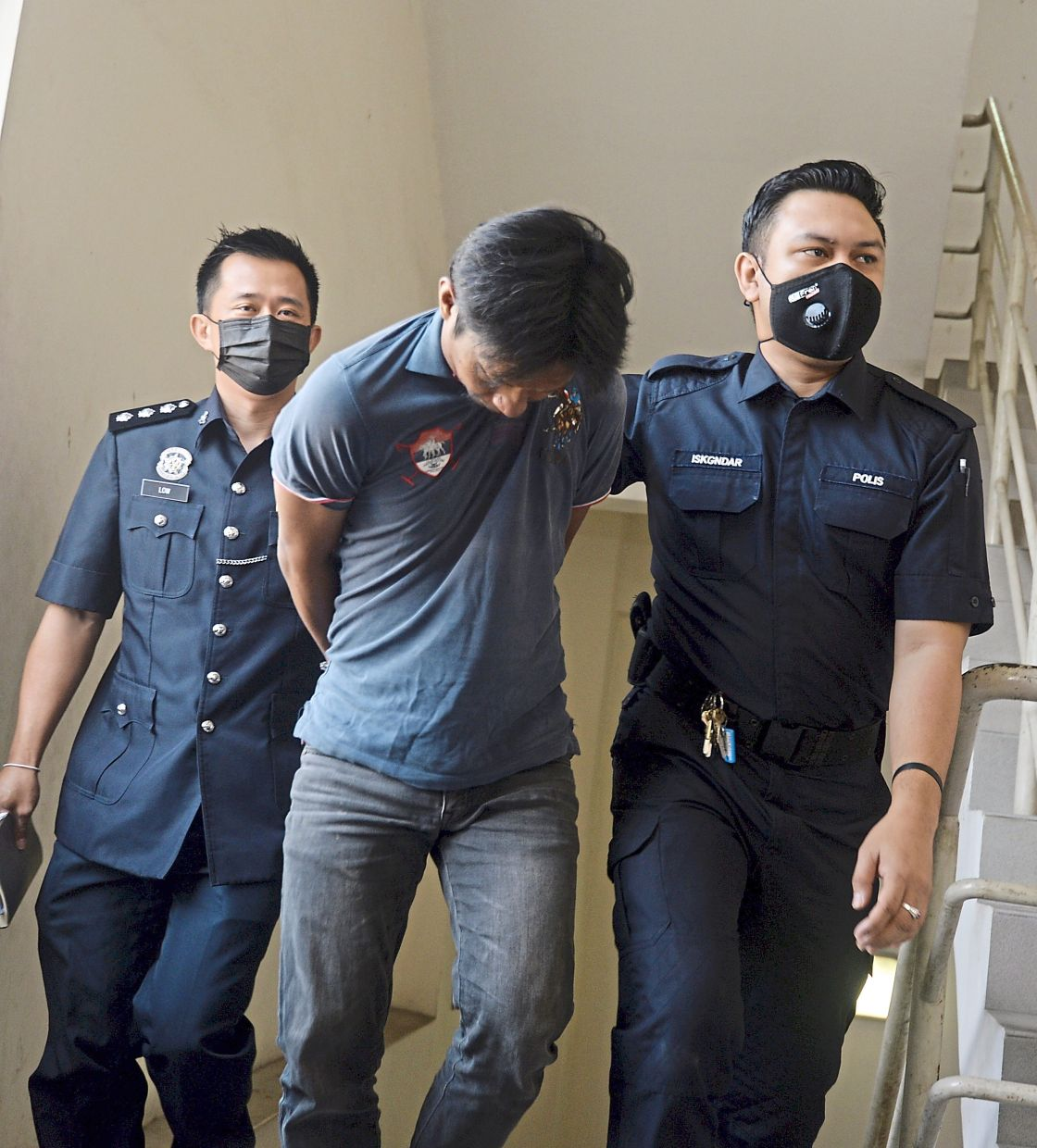 Facing the law: Police officers escorting Mohamed Badruldin to the Magistrate's Court in Petaling Jaya. — SS KANESAN/The star