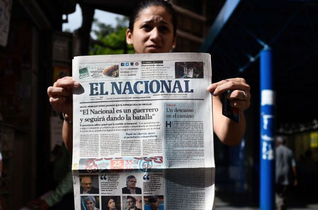 """In this file photo taken on December 14, 2018, a woman shows the last printed edition of Venezuelan newspaper El Nacional with its front page reading \""""El Nacional is a worrior and will keep on fighting\"""" at a newspaper stand in Caracas. - Venezuelan justice on Friday seized the headquarters of the newspaper El Nacional, a critic of the government of Nicolás Maduro, to cover the 13 million dollars that a court ordered it to pay to the number two of chavismo in a defamation lawsuit. - AFP"""