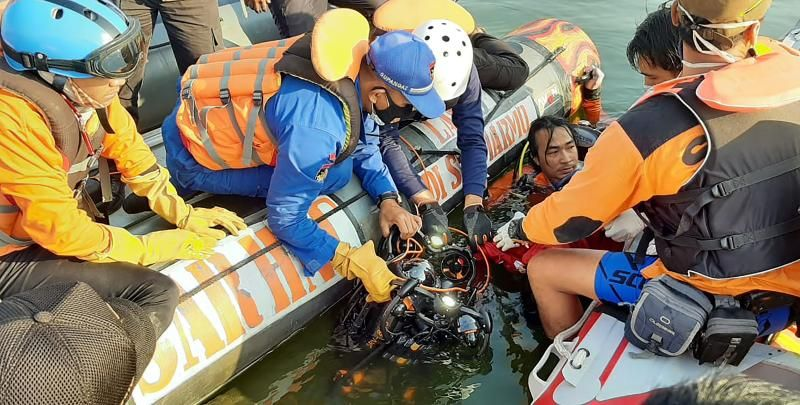 This handout photo taken on May 16, 2021 and released by National Search and Rescue Agency (BASARNAS) shows rescuers searching for victims after a boat carrying 20 holiday-makers capsized on May 15 at a reservoir in Boyolali, Central Java. - AFP