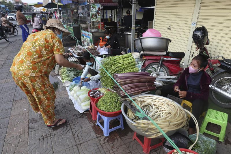 A vendor, right, sells fresh vegetable along a street in Phnom Penh. Cambodia is battling a surge of Covid-19 cases, so there are restrictions in Phnom Penh that close many food markets and shops, giving more mobile street vendors an opportunity to do business, even if they have to dodge police in areas where they may be breaking the law. - AP