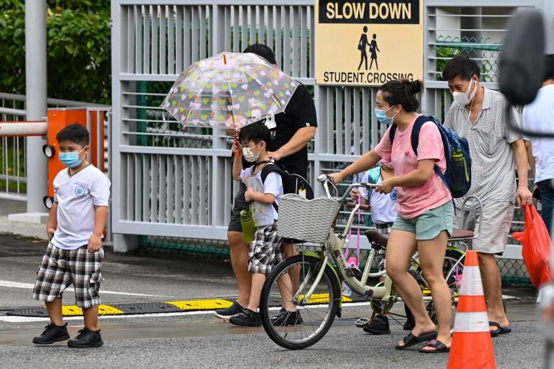 Children walk home with their guardians after school in Singapore on May 17, 2021, as the country prepares to shut all schools and switch to home-based learning until the end of the term due to a rise in the number of Covid-19 coronavirus cases. - AFP