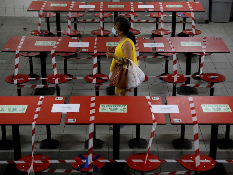 A woman walks between rows of taped up tables at a food centre as dining-in is restricted to curb the coronavirus disease (COVID-19) outbreak in Singapore May 17, 2021. - Reuters