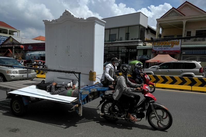 A worker takes a nap beside a wardrobe being transported on a motor-cart in Phnom Penh on Tuesday, May 18, 2021. - AFP