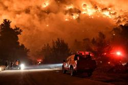 Greece evacuates more as forest fire spreads to Attica region